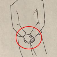 股間の前で腕を組む
