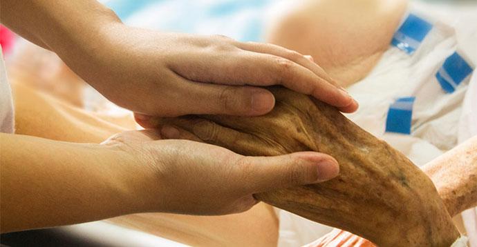 患者の手を握る